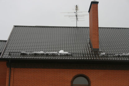 Кирпичный дом со снегозадержателями на крыше
